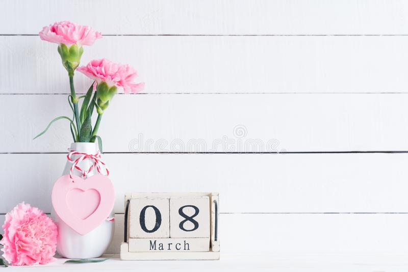 Womans day concept. Pink carnation flower in vase and red heart with March 8 text on wooden block calendar on white wooden royalty free stock photography