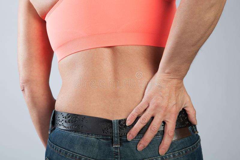 Womans dorsal pain. A woman has some dorsal pain and is touching her back stock photos