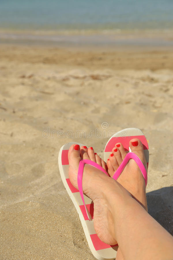 Womans feet with flip flops. On the sand royalty free stock image