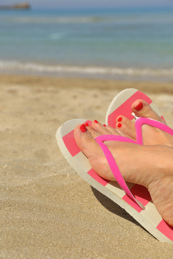 Womans feet with flip flops. On the sand royalty free stock images