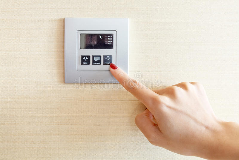Womans finger på luftkonditioneringsapparatströmbrytarekontroll arkivfoton