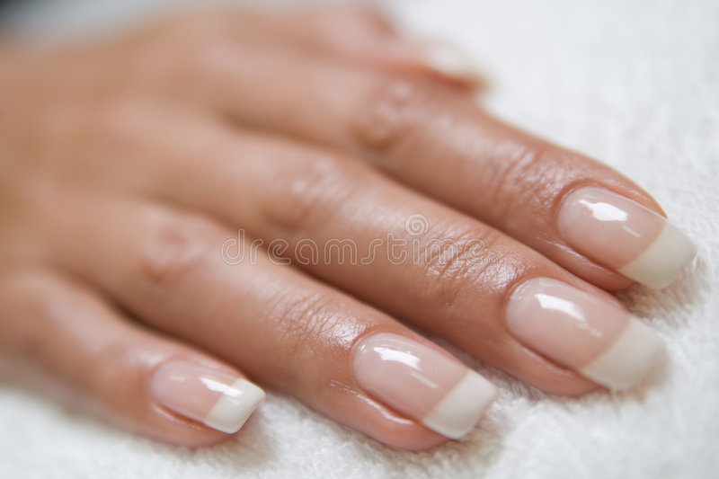Womans hand. With a french manicure on the towel stock images