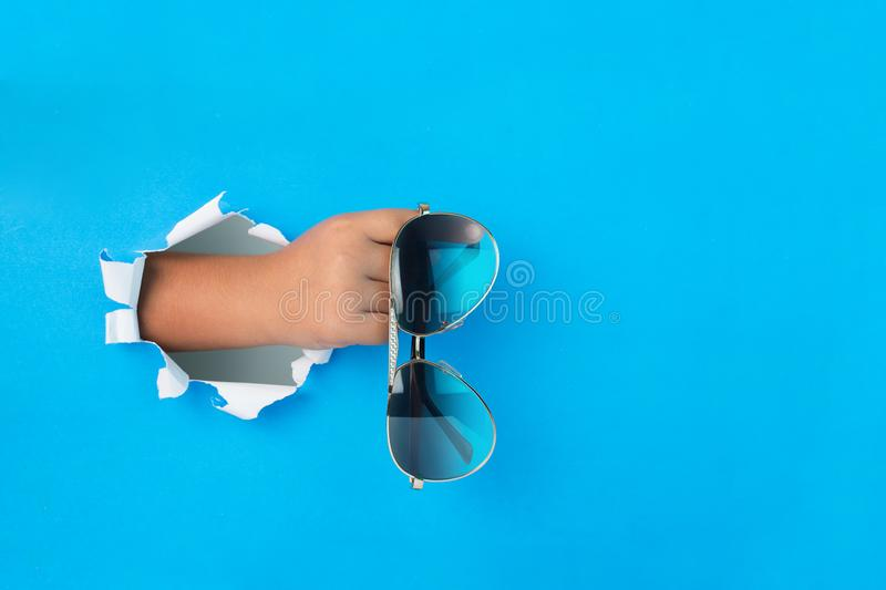 Womans hand breaking through paper holding fashionable pair of sunglasses in a fist. Fashion / lifestyle concept image with copy space for text stock photography