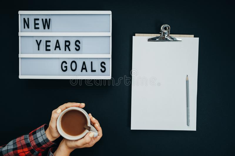 Womans hand with cocoa and Board with. `GOALS` text, notebook, pencil on black background, top view, flat lay stock photo