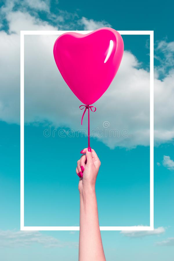 Womans hand with heart shaped balloon on background of sky. Love concept royalty free stock photography