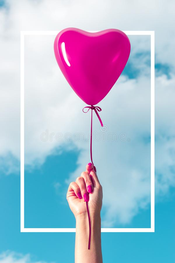 Womans hand with heart shaped balloon on background of sky. Love concept.  stock image
