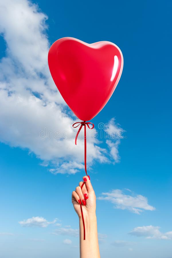 Womans hand with heart shaped balloon stock photos