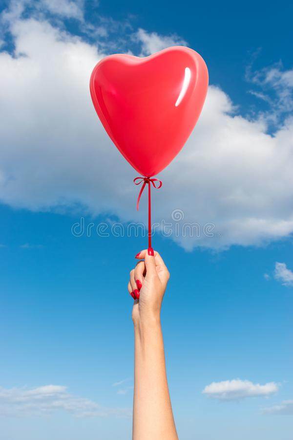 Womans hand with heart shaped balloon stock photography