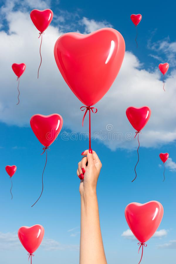 Womans hand with heart shaped balloons stock photography
