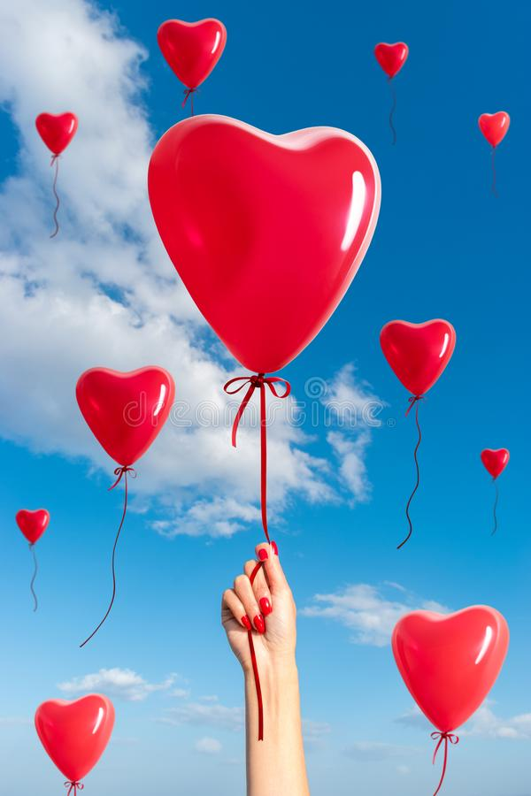 Womans hand with heart shaped balloons stock image