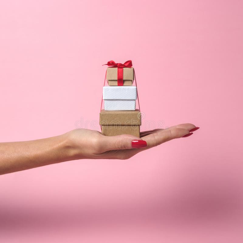 Womans hand holding gift boxes on pink background. Minimal sale concept stock images