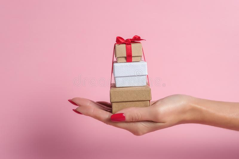 Womans hand holding gift boxes on pink background. stock photos