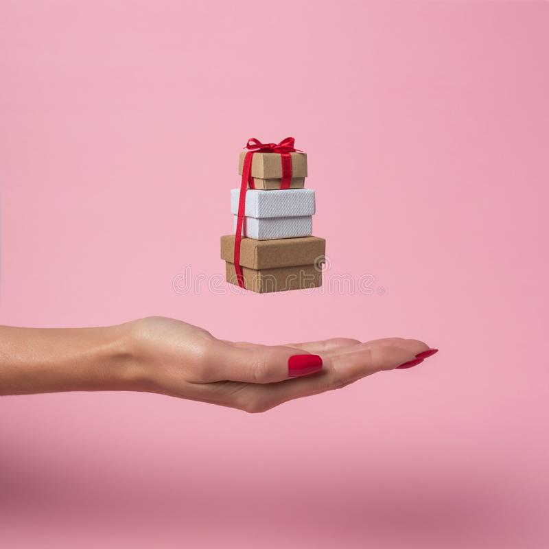 Womans hand holding gift boxes on pink background. Minimal sale concept stock photo