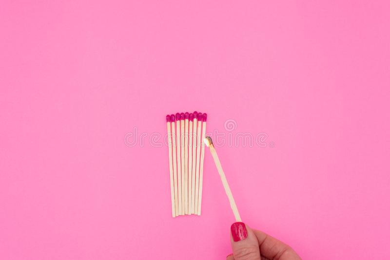 Womans hand holding lit matchstick royalty free stock photography