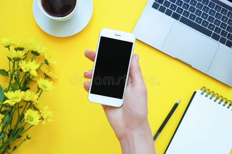 Womans hand holding a phone at the table office. Yellow background. Womans hand holding a phone at the table office. Yellow background royalty free stock photo