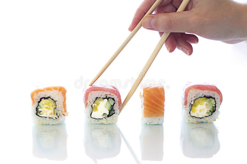 Womans hand is holding Sushi roll with chopsticks. Japanese food. Close up stock image