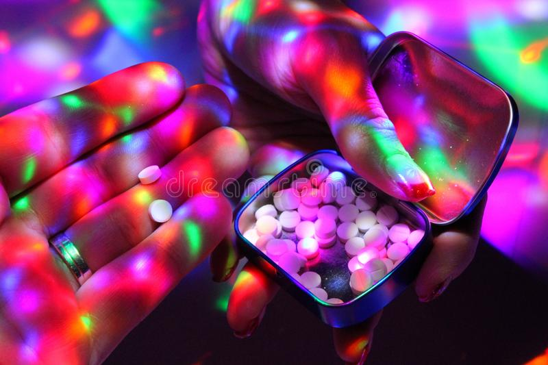 A man takes ecstasy from the box the dealer holds. Womans hand with nice nails offers ecstasy on a disco royalty free stock image