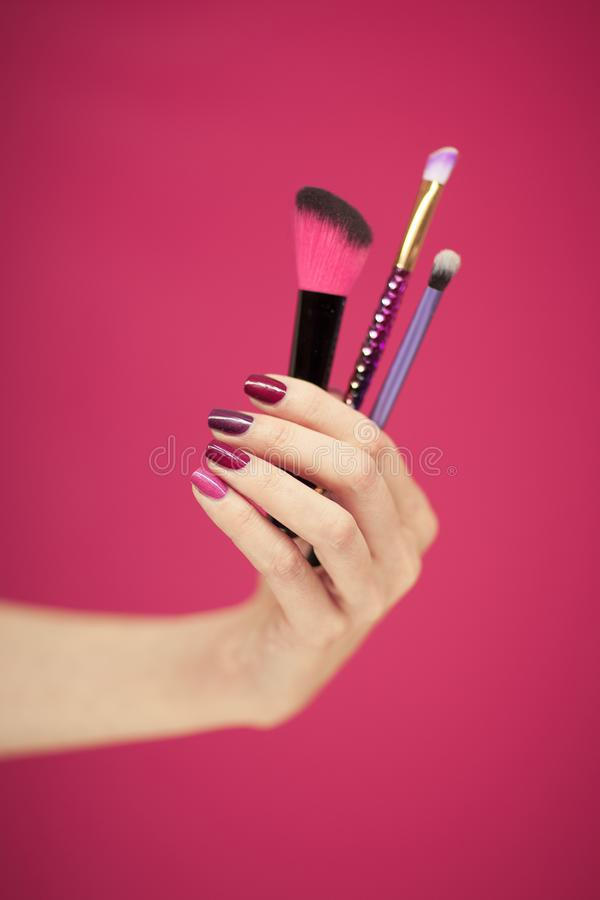 Womans hand with perfect pink nail polish holding cosmetic brushes. In front of pink background royalty free stock images