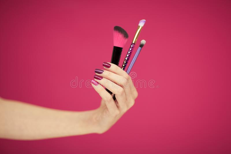 Womans hand with perfect pink nail polish holding cosmetic brushes. In front of pink background stock photo