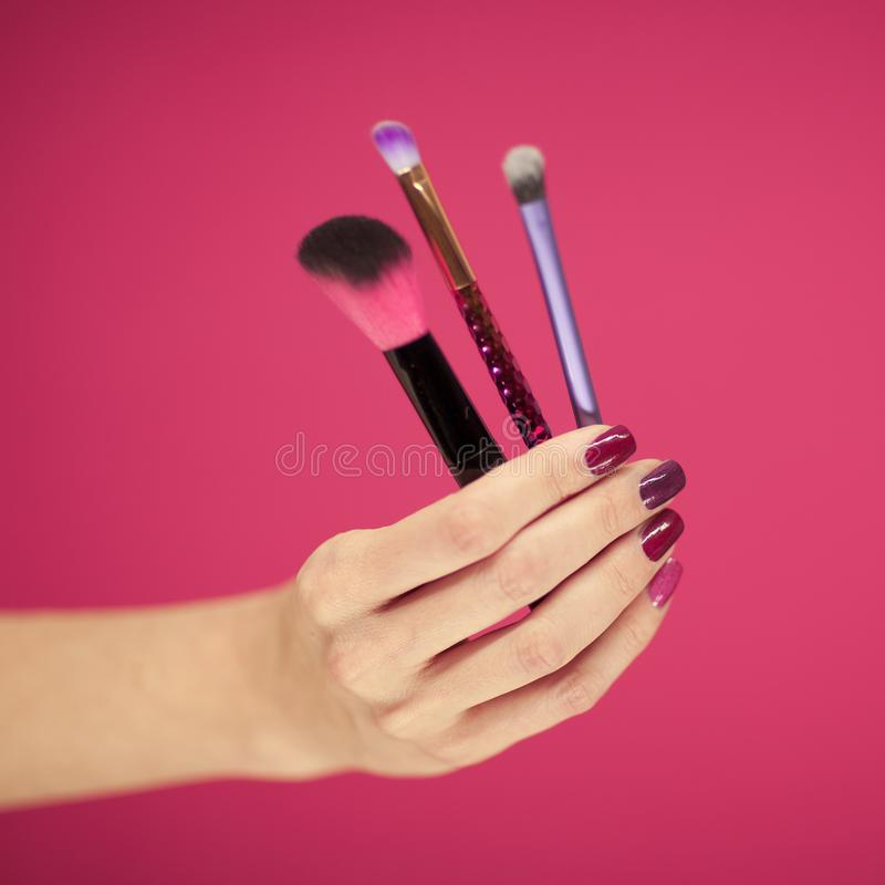 Womans hand with perfect pink nail polish holding cosmetic brushes. In front of pink background stock images