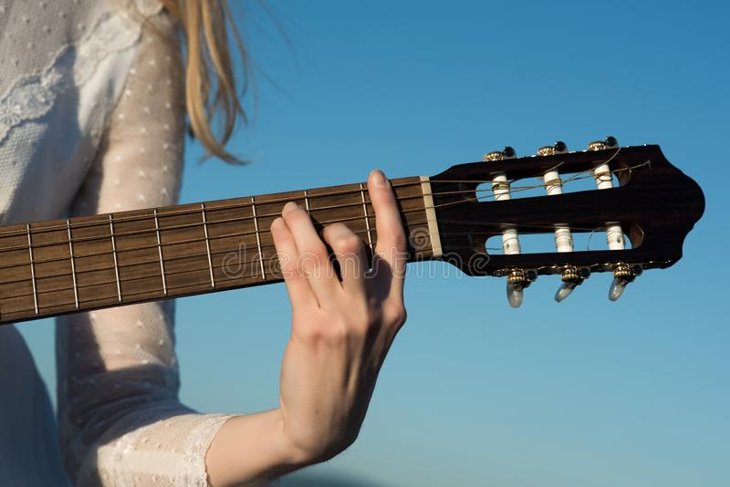 Womans hand playing acoustic guitar instrument, closeup stock photo