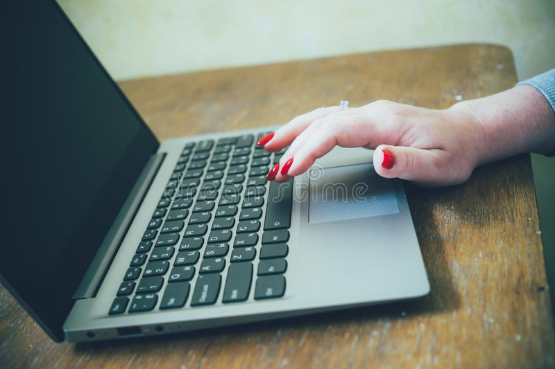 Womans hand with red nails on laptop keyboard, lady using laptop on old vintage table. Close-up stock images
