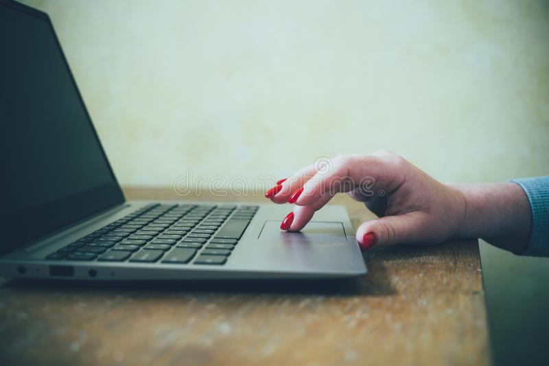 Womans hand with red nails on laptop keyboard, lady using laptop on old vintage table. Close-up royalty free stock images