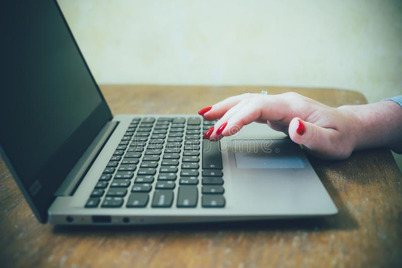 Womans hand with red nails on laptop keyboard, lady using laptop on old vintage table. Close-up stock photography
