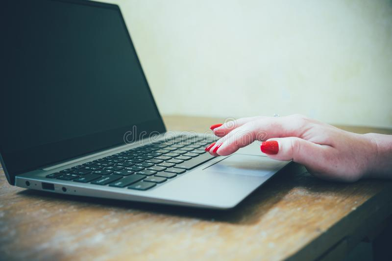 Womans hand with red nails on laptop keyboard, lady using laptop on old vintage table. Close-up stock photo