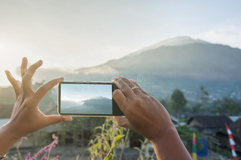 Womans hand taking photo of mouintain in late afternoon with phone. Modern technology and lifesyle concept stock photo