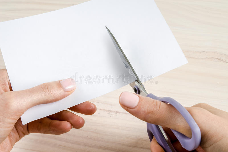 Female hands cutting paper with scissors. Female hands cutting blank paper or card with a pair of purple handed scissors with wood background royalty free stock photos