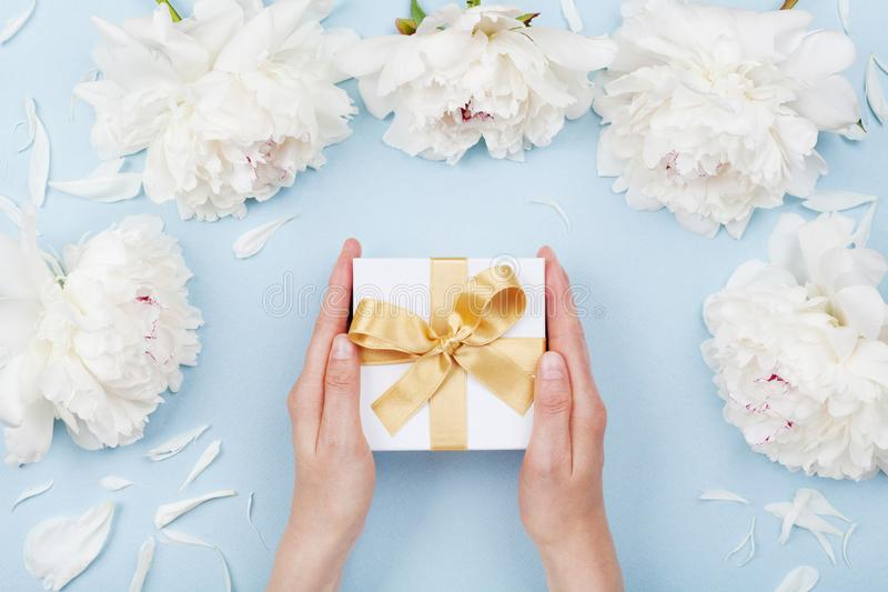 Womans hands giving gift or present box decorated white peony flowers on pastel table top view. Flat lay composition for birthday. Or wedding stock images