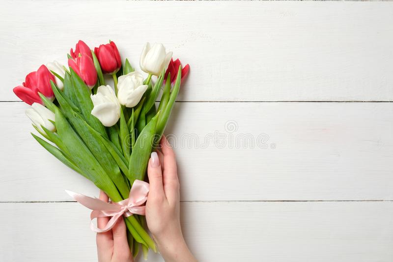 Womans hands holding Bouquet of tulips on white wooden horizontal striped board. Greeting card for International Womans Day, Mothe stock images