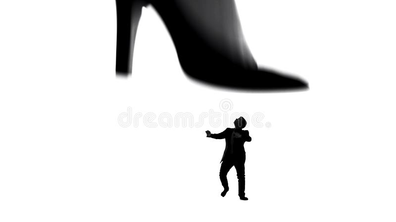Womans leg in high heels stepping on small weak man, female dominating in couple. Stock photo stock image
