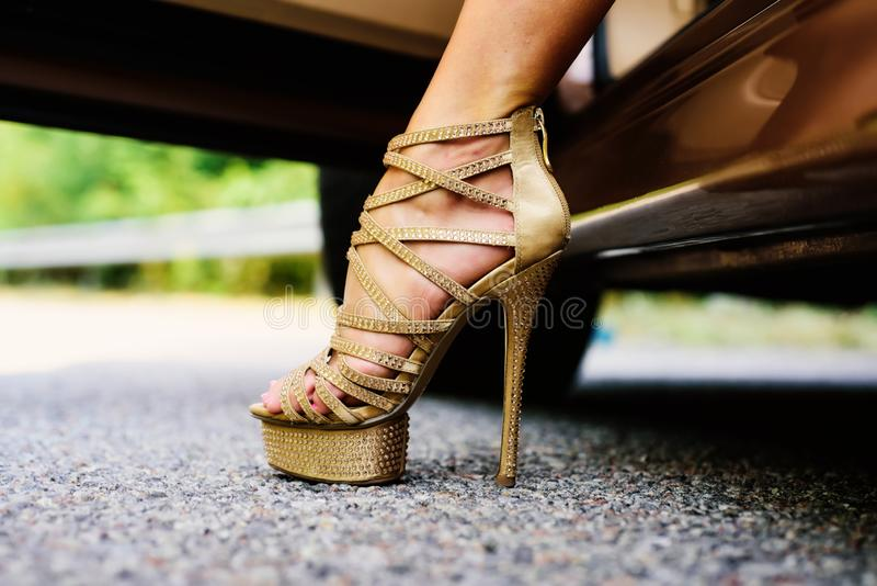 Womans legs in high heels. Luxury urban background. The woman is wearing shoes on high heels. Close up of woman legs royalty free stock photography