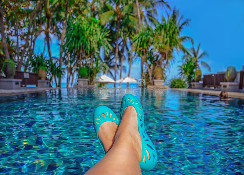 Womans legs lying down on a sunlounger looking over the water. Sunbathing by the hotel tourist resort swimming pool . Womans legs lying down on a sunlounger stock photos