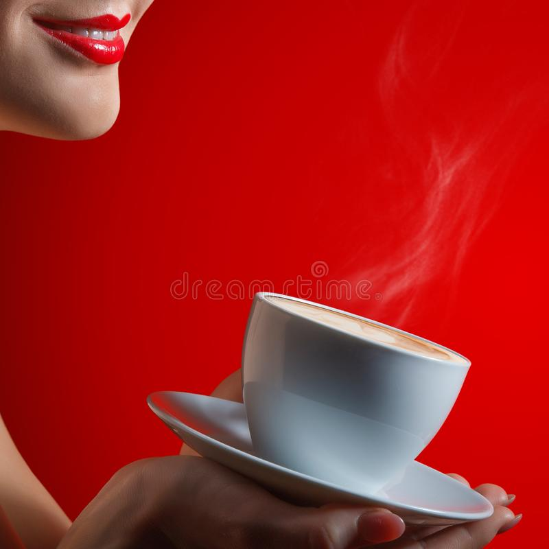 Womans smile lips and cup with coffee cappuccino in hand in studio at the red background. Close up royalty free stock photos