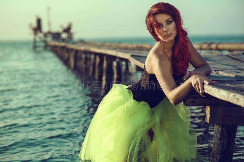 Womanstanding de cabelo vermelho na água do mar que inclina-se no cais Sereia que sai da água e que tenta fazer primeiras etapas imagens de stock royalty free