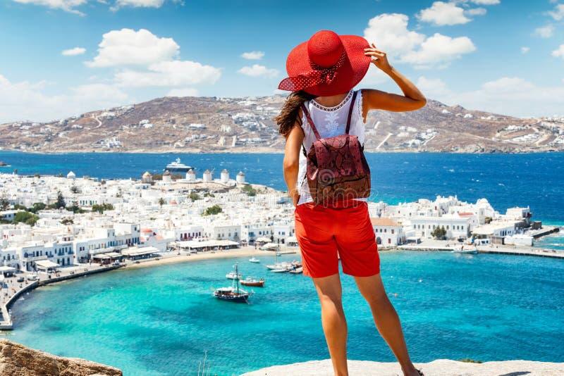 Womanstands på en kulle över den härliga staden av den Mykonos ön fotografering för bildbyråer