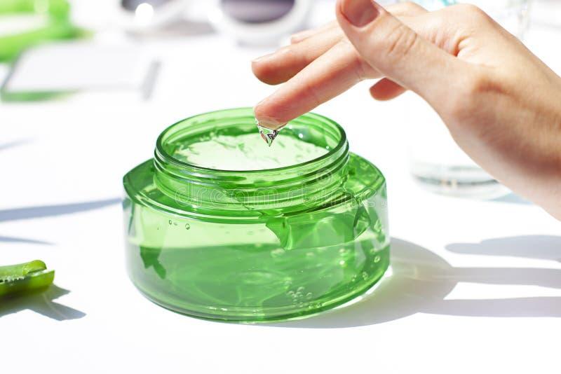 Womas ręka zamacza palec w kosmetycznym aloesu Vera gel w przejrzystym słoju zamkniętym w górę obraz royalty free