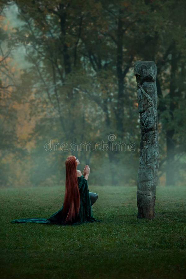 Womderful ung flickaliv i en dimmig skog, kommer till en röjning på en kulle till en gud för bön, en trollkvinna med royaltyfria foton