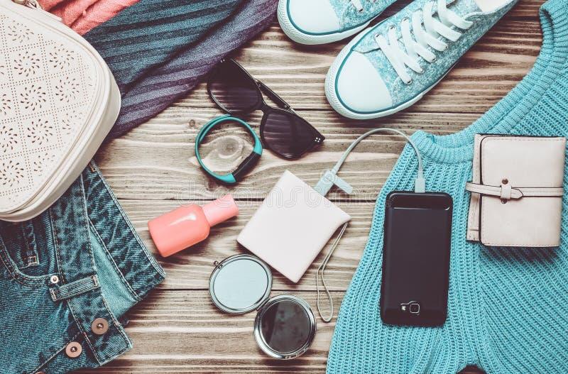 Women& x27 καθιερώνοντα τη μόδα εξαρτήματα του s, παπούτσια, ενδύματα και σύγχρονες συσκευές σε ένα ξύλινο υπόβαθρο Τζιν, τσάντα, στοκ φωτογραφία