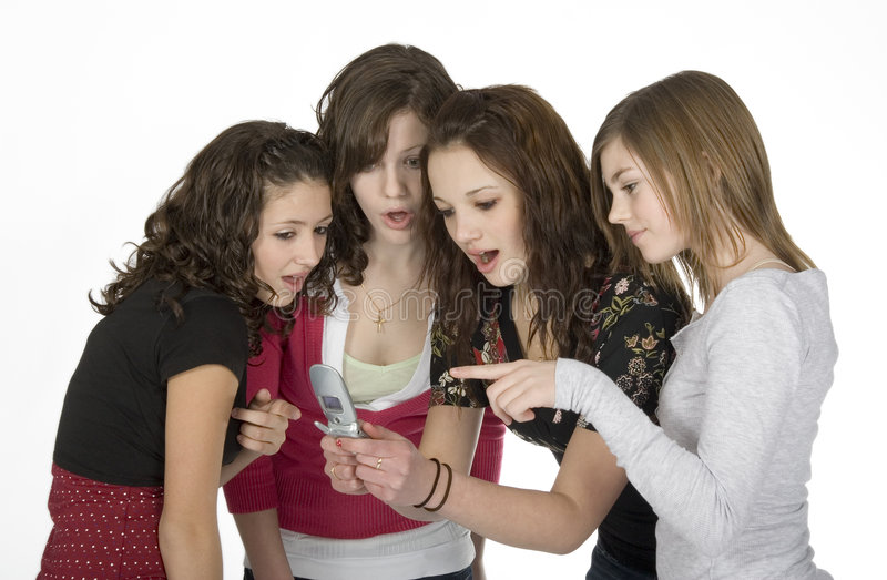 Women. Four young women looking at picture on cell phone royalty free stock photography