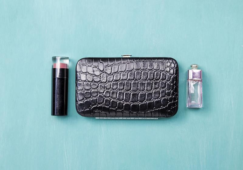 Shiny black leather purse with lipstick and perfume. Women accessories on blue background, Shiny black leather purse with lipstick and perfume on blue background stock photography