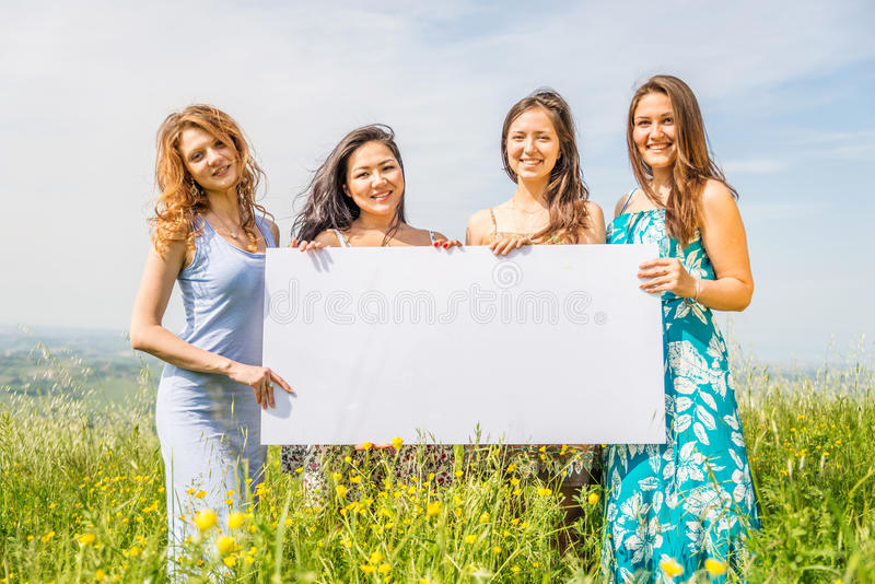 Women with advertising board. Group of multiethnic girls holding blank advertising board in a flowers field - Four beautiful and happy women promoting something royalty free stock photo