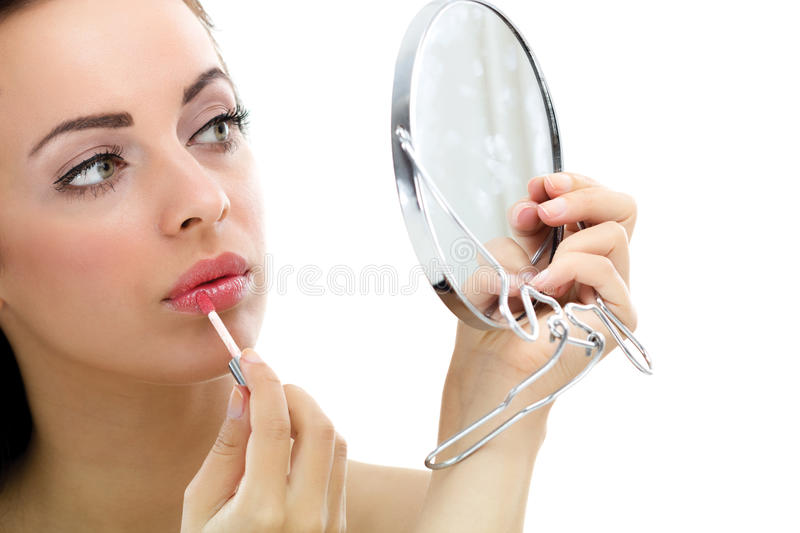 Women apply lipstick in front of mirror