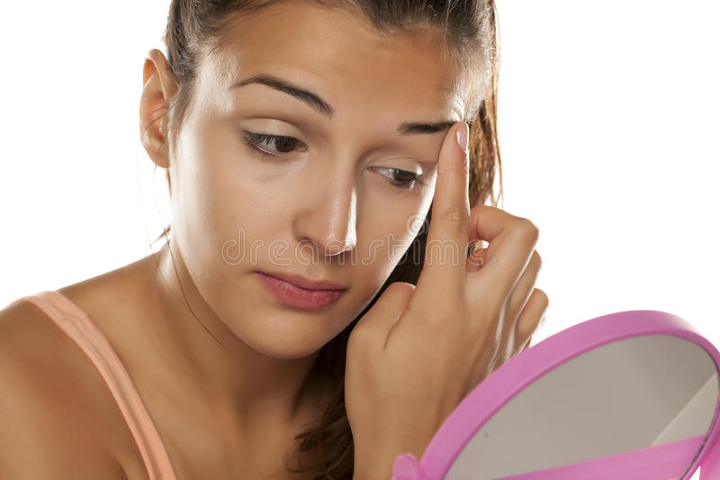 Women applying concealer. Young woman applying concealer around her eyes using her finger stock photos