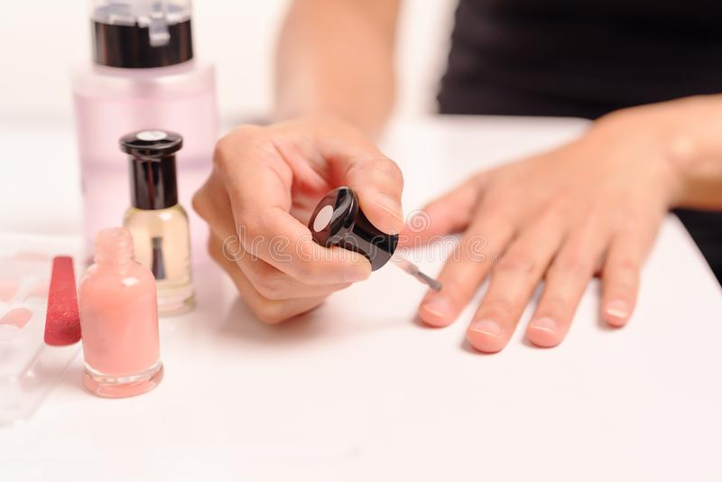 Women applying nail polish on white table with bottles of nail polish and remover, fashion and beauty concept royalty free stock photo