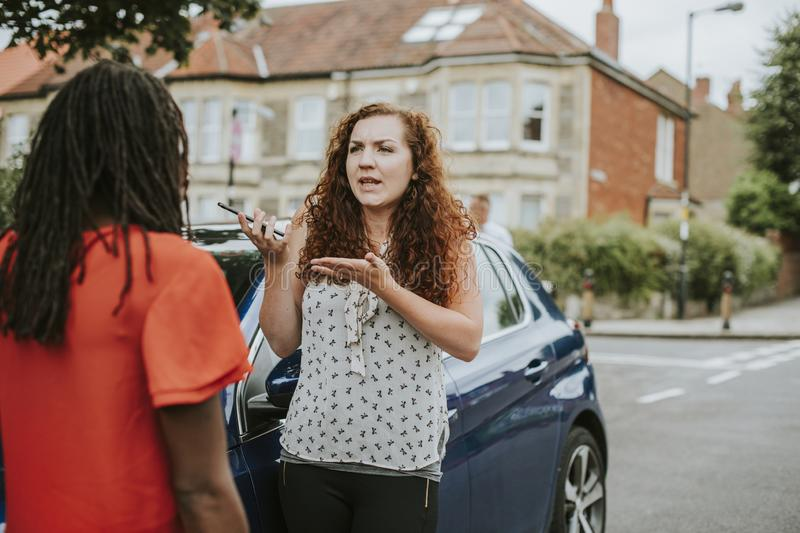 Women arguing after a car accident stock photography