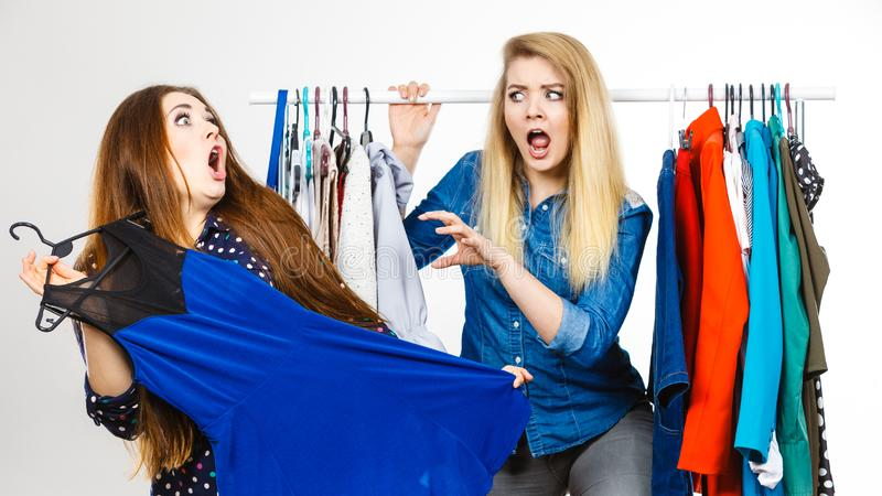Women arguing during clothes shopping royalty free stock image